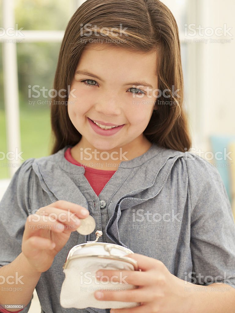 Smiling girl putting money into coin purse stock photo