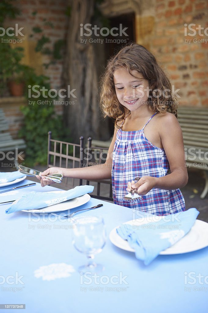 Smiling girl setting table outdoors stock photo