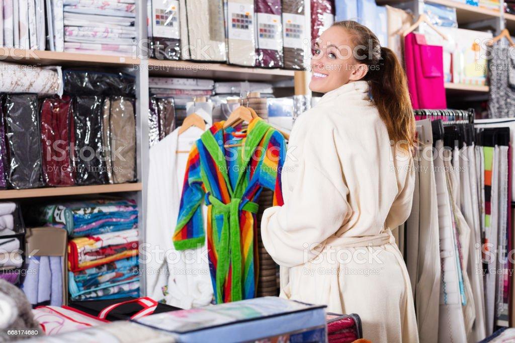 Smiling girl shopper examining new bathrobe stock photo