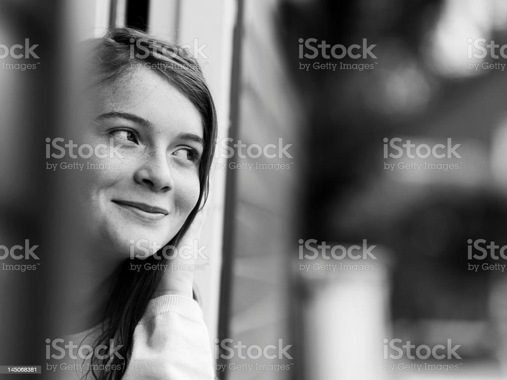 Smiling girl standing in doorway stock photo