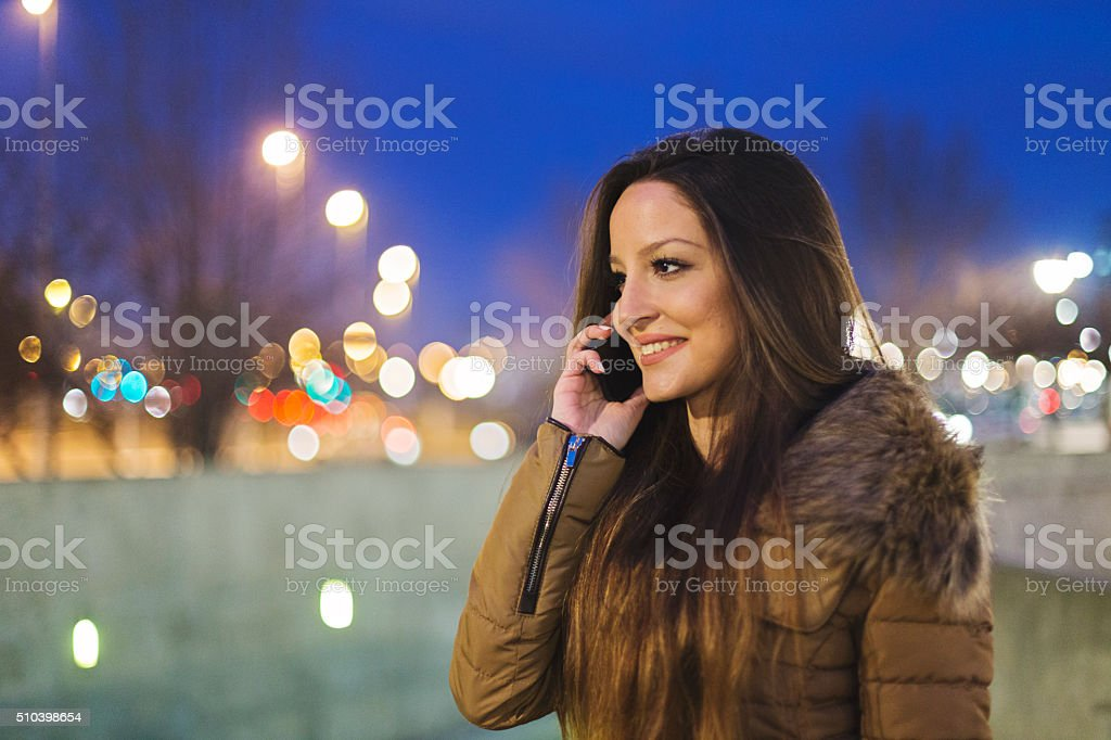 Smiling girl talks on smart phone stock photo