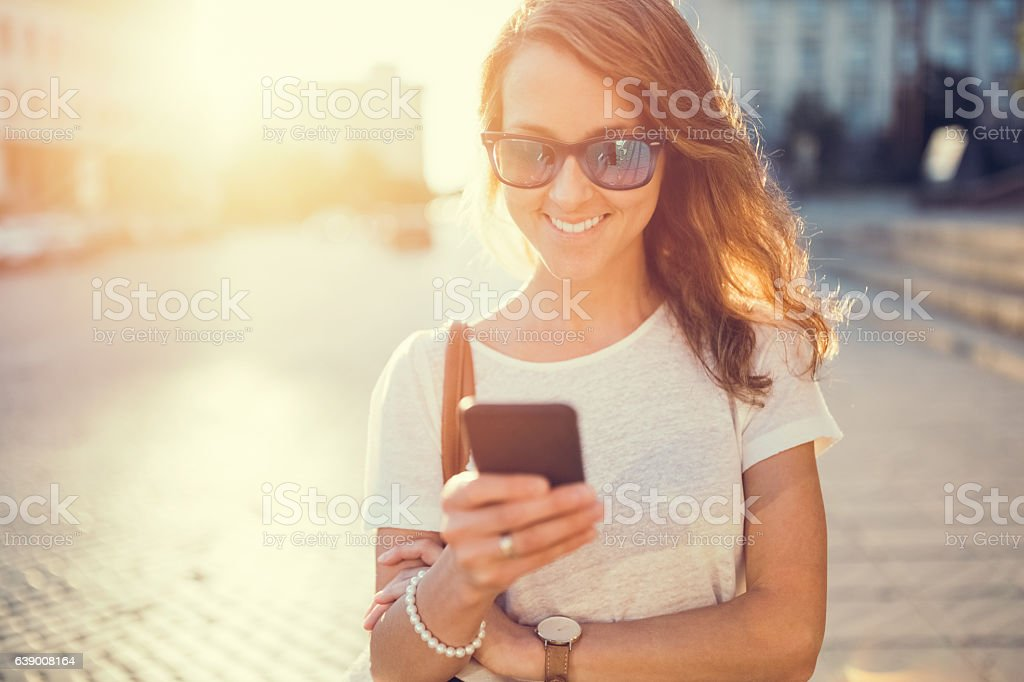 Smiling girl texting at the street stock photo