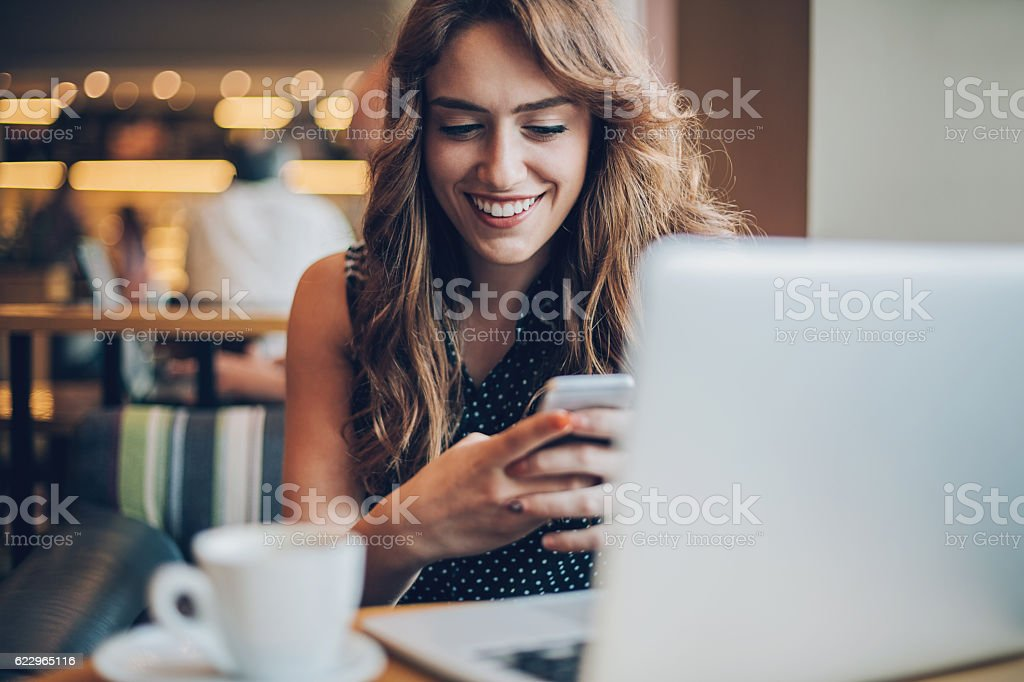 Smiling girl texting in cafe stock photo