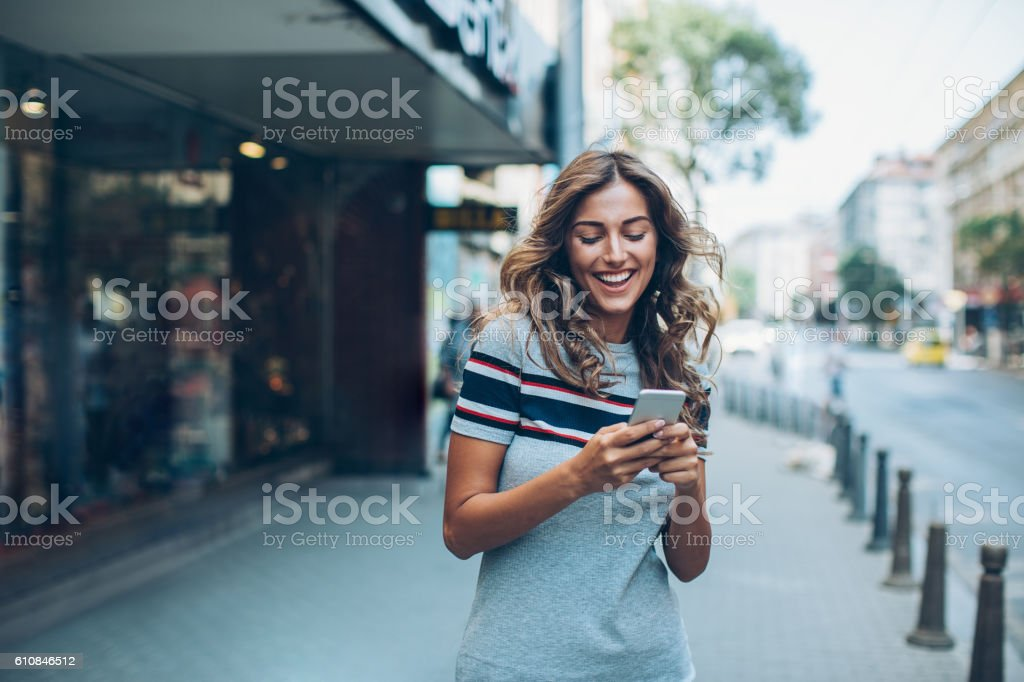 Smiling girl texting on the street stock photo