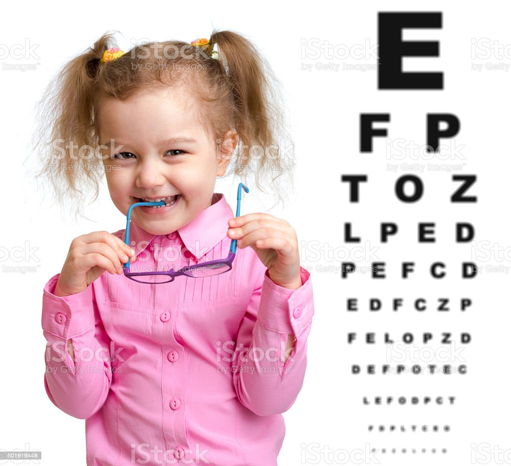 Smiling girl took off glasses with blurry eye chart behind stock photo
