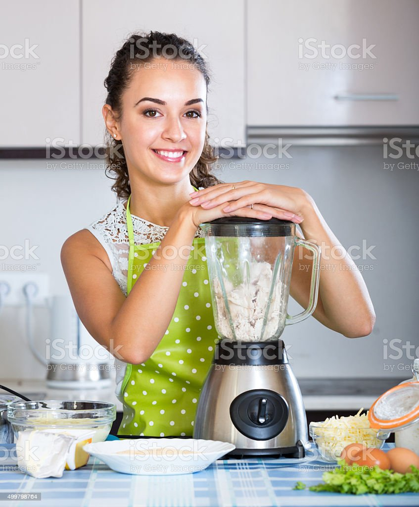 Smiling girl using kitchen blender for cooking stock photo