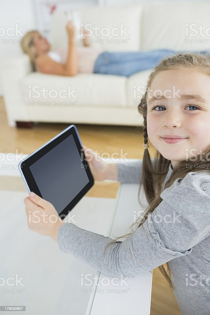 Smiling girl using tablet computer while mother is reading royalty-free stock photo