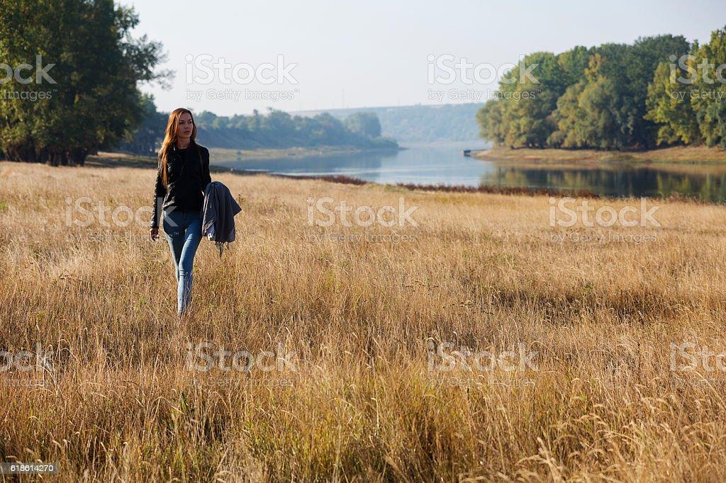 Smiling girl walking at autumn meadow stock photo