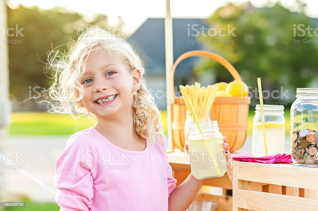 Smiling girl with blonde curly hair holding up lemonade stock photo