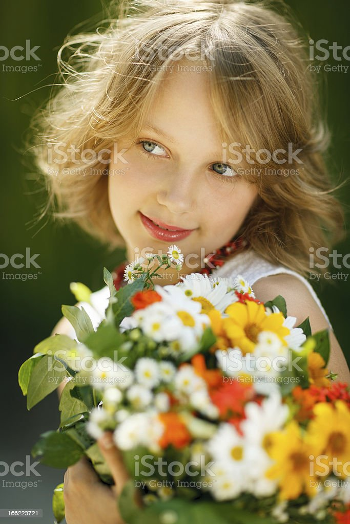 Smiling girl with bunch of wildflowers royalty-free stock photo