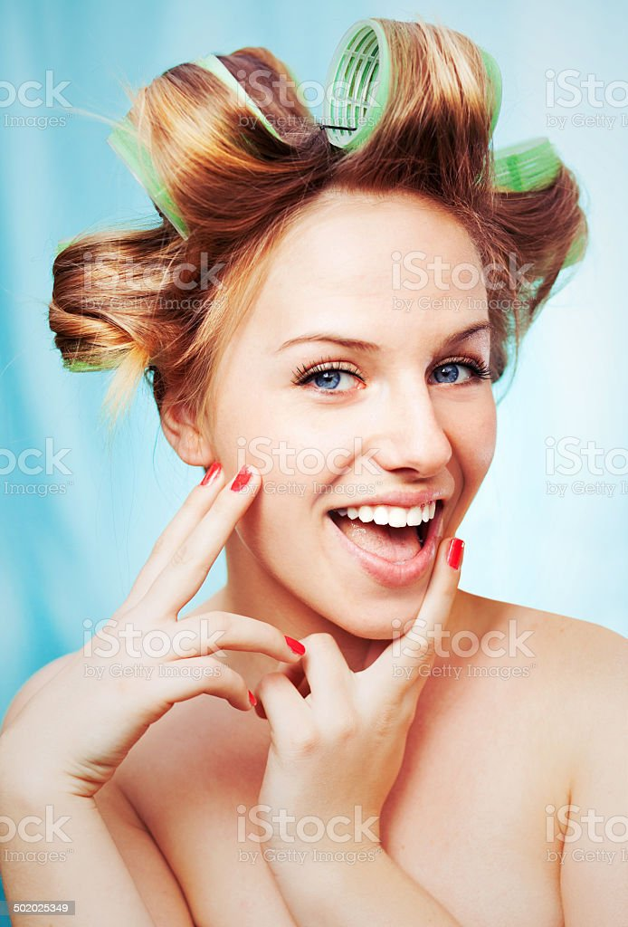 Smiling girl with curlers stock photo