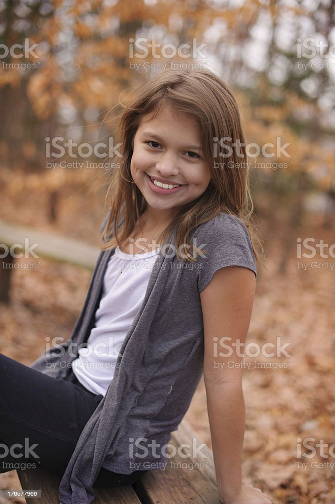 Smiling Girl with Dimples Sitting Outside During Fall royalty-free stock photo
