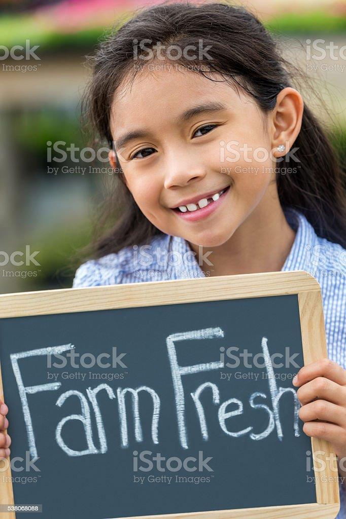 Smiling girl with Farm Fresh sign stock photo