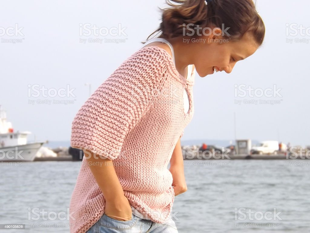Smiling girl with knitted top at the wharf. royalty-free stock photo