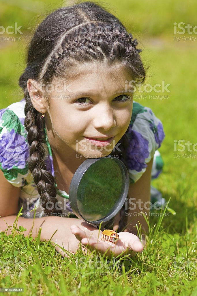Smiling girl with magnifying glass royalty-free stock photo