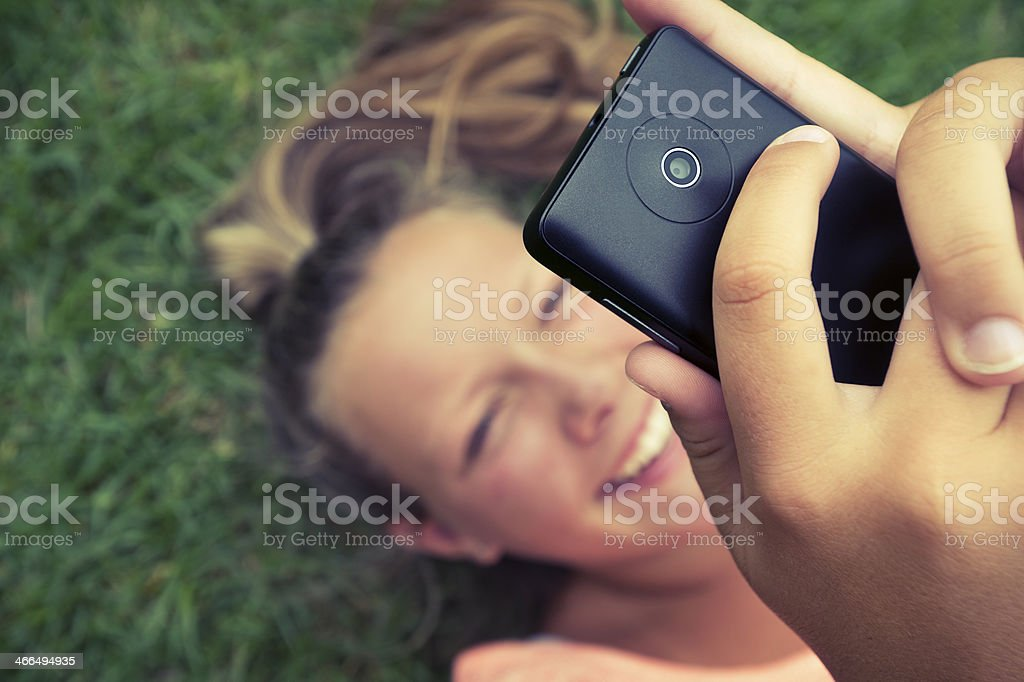 Smiling girl with mobile phone in the grass royalty-free stock photo