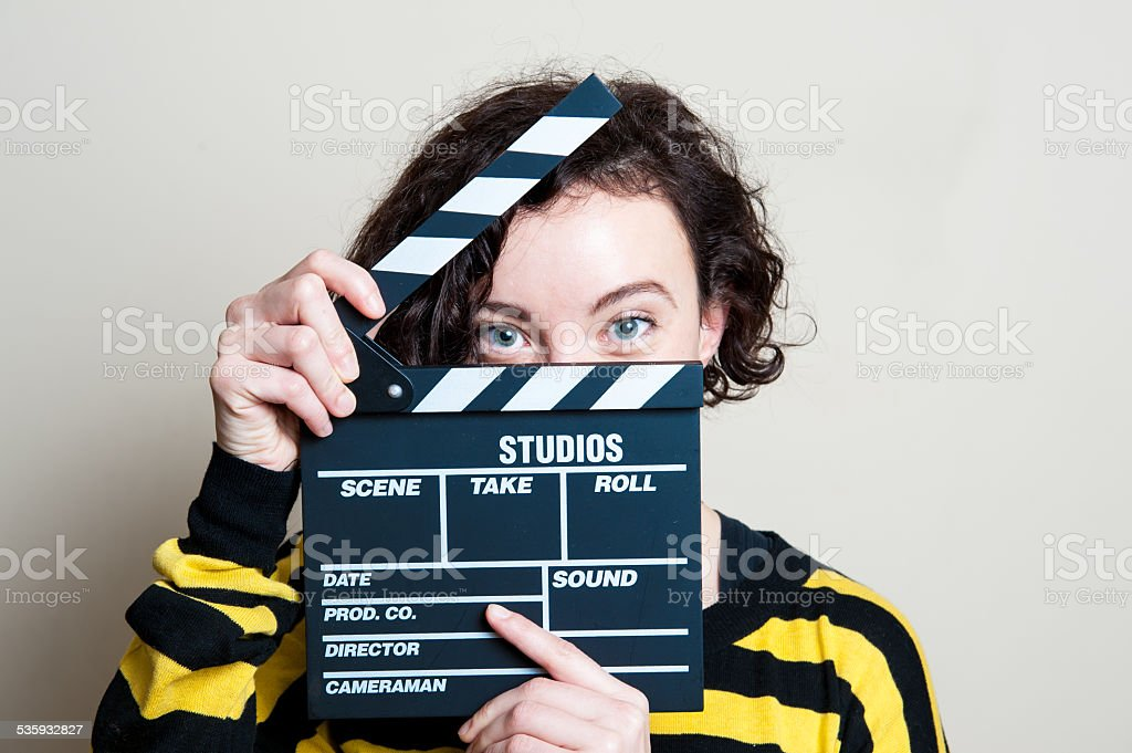 Smiling girl with movie clapper on white background stock photo