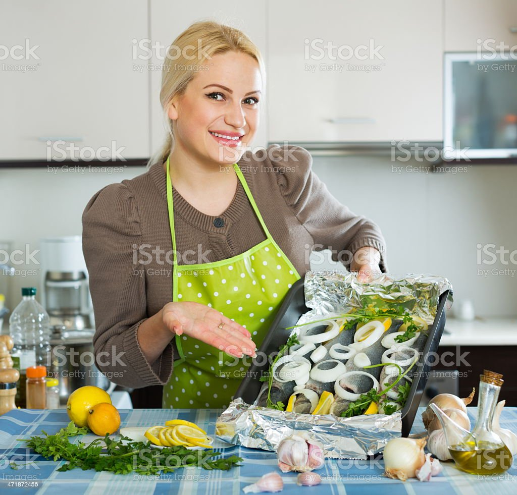 Smiling girl with raw fish stock photo