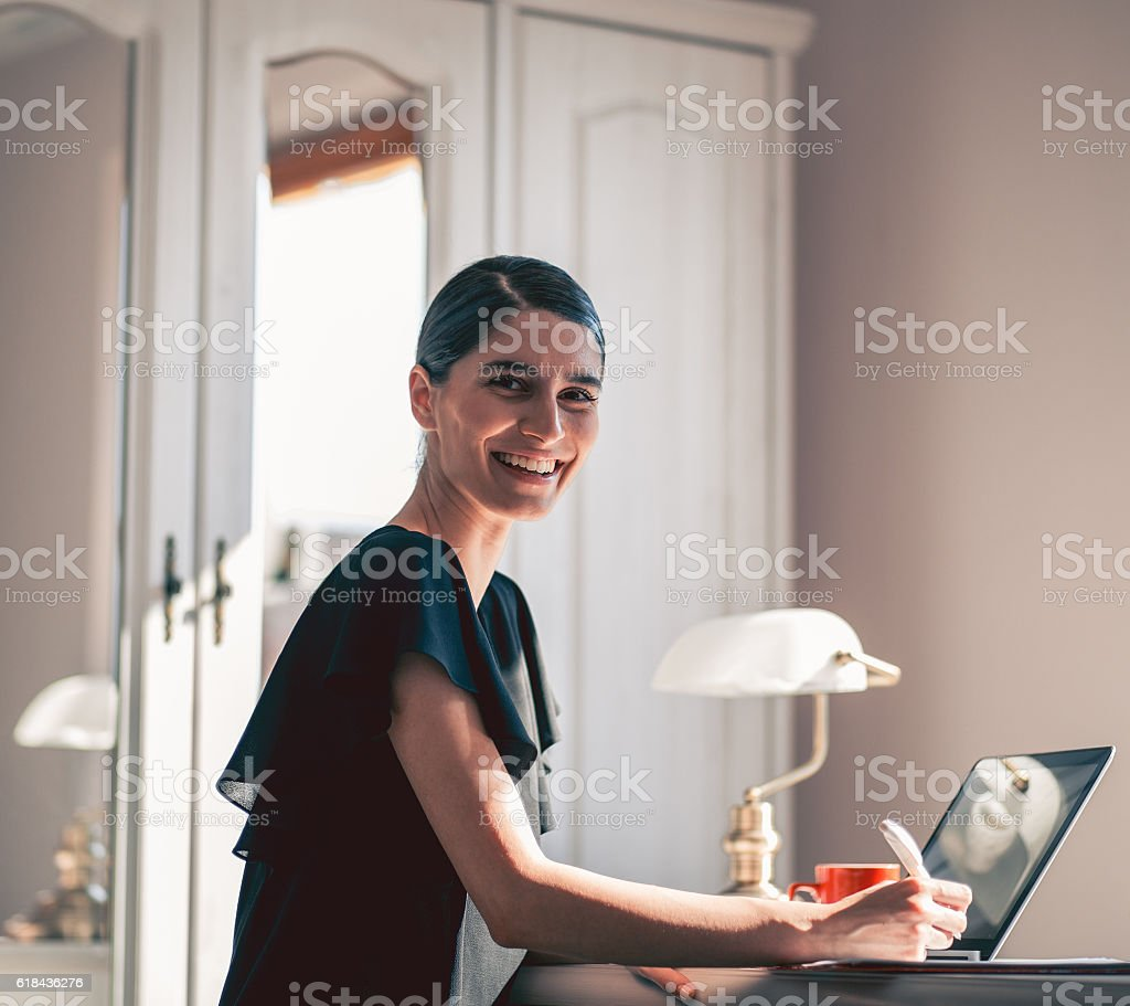 smiling girl working at desk stock photo