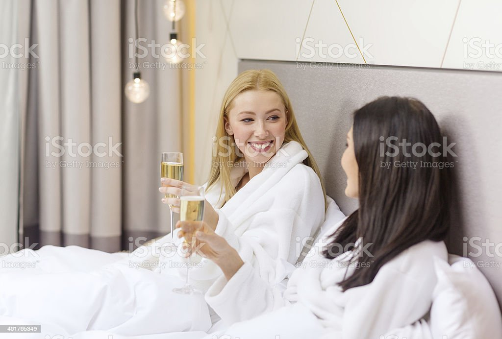 smiling girlfriends with champagne glasses in bed stock photo