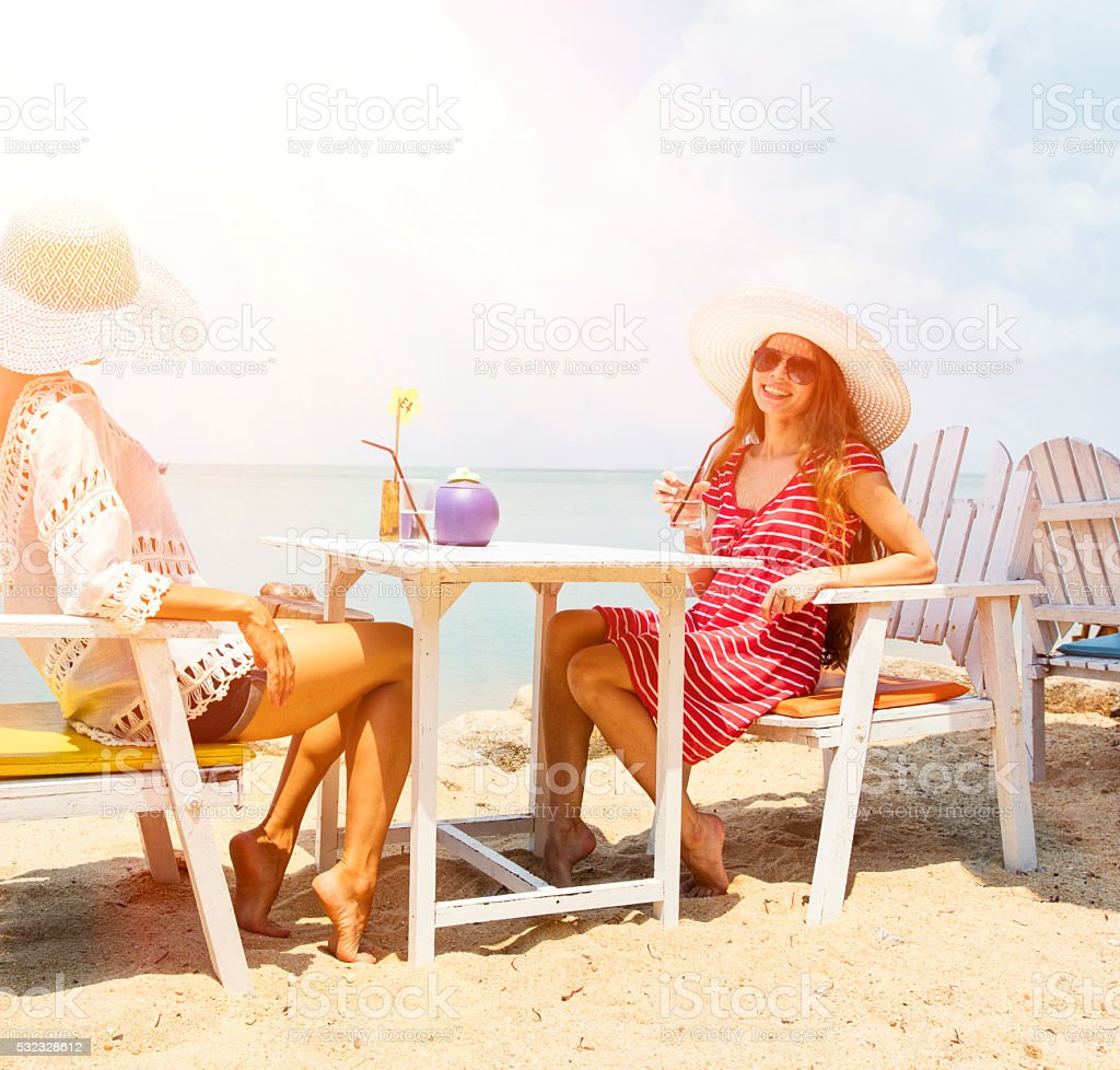 smiling girls in cafe on the beach stock photo