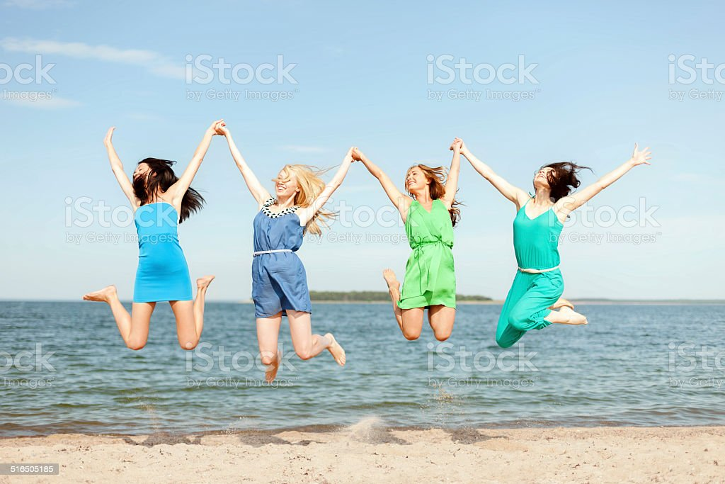 smiling girls jumping on the beach stock photo