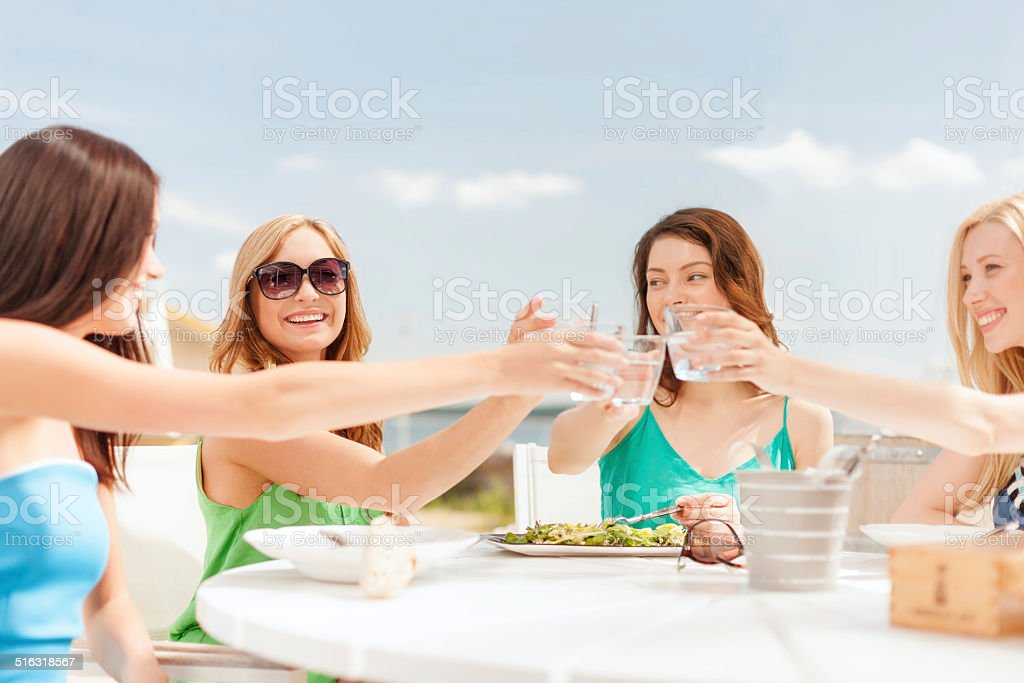 smiling girls looking at tablet pc in cafe stock photo