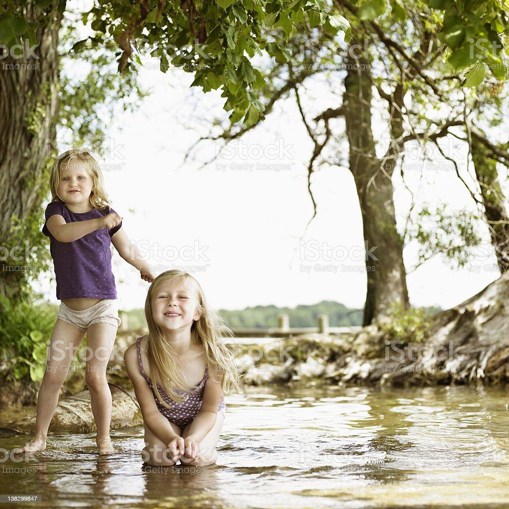 Smiling girls playing in lake stock photo