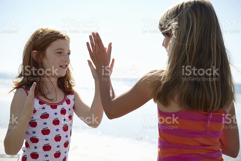 Smiling girls playing together on beach stock photo