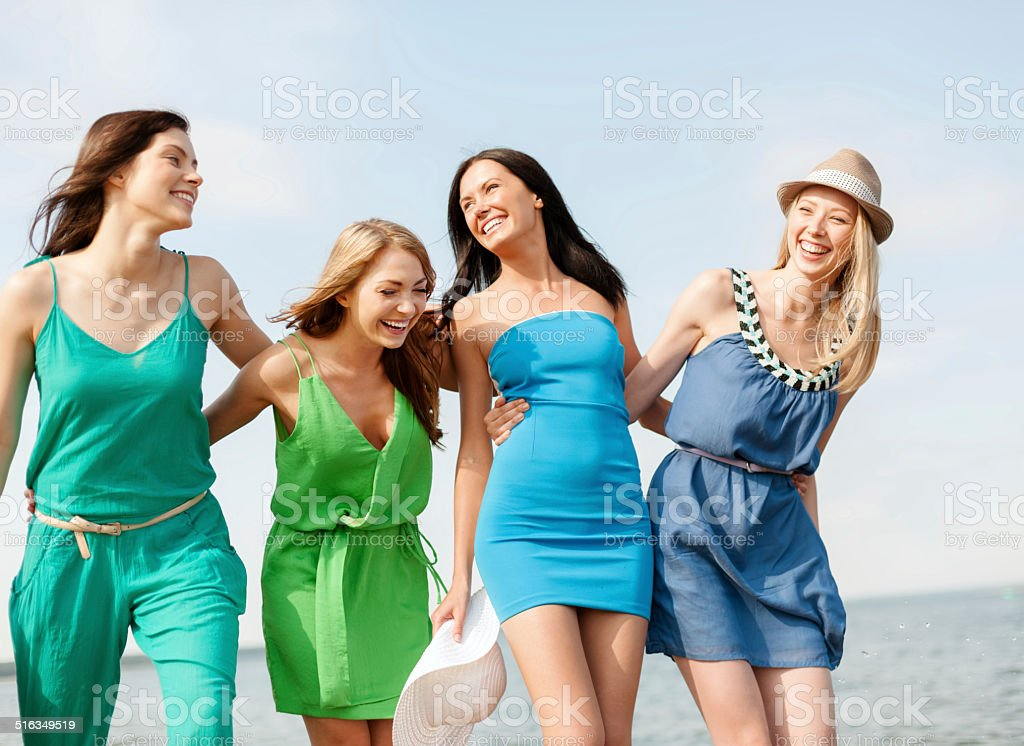smiling girls walking on the beach stock photo