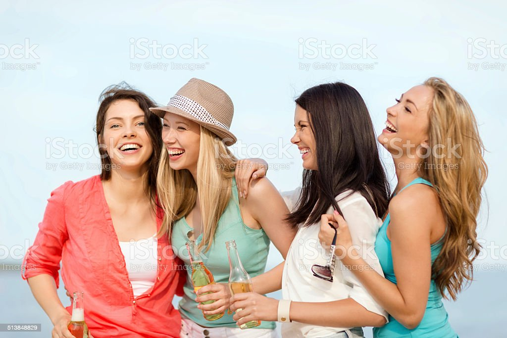 smiling girls with drinks on the beach stock photo