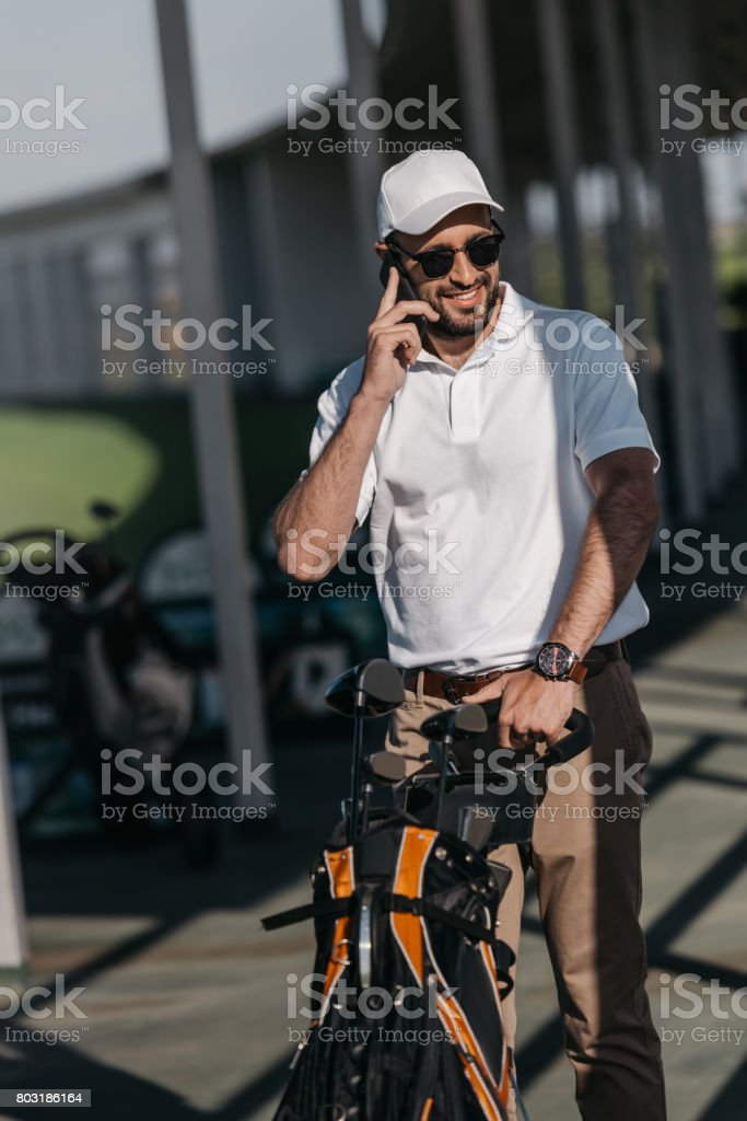 smiling golf player talking on smartphone before golf game stock photo