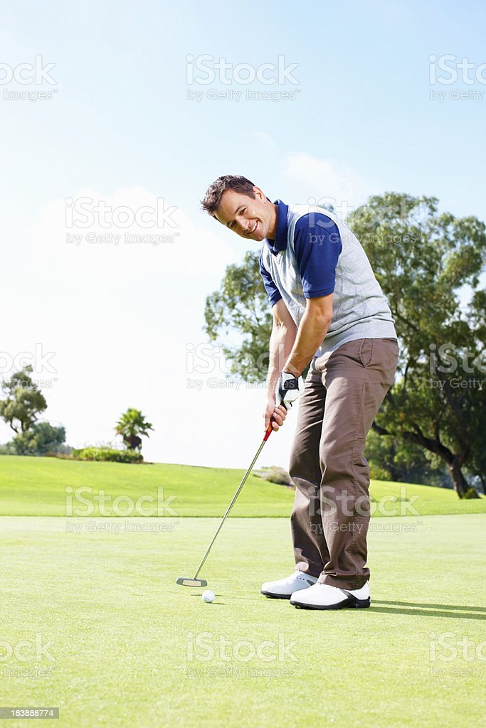Smiling golfer putting the ball royalty-free stock photo