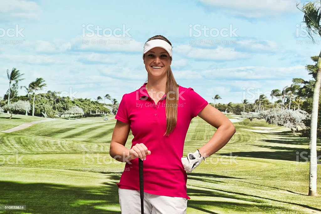 Smiling golfer standing at field stock photo