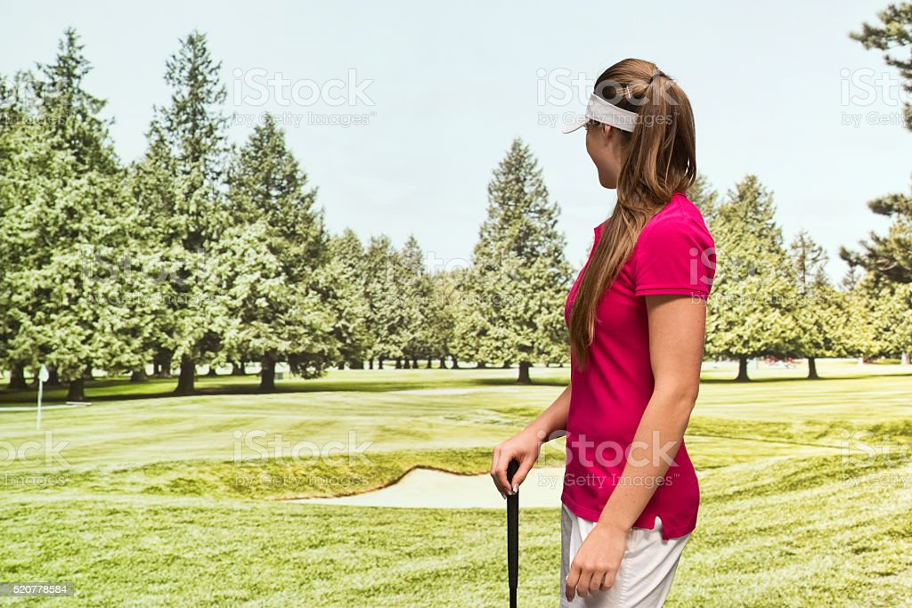 Smiling golfer standing in field stock photo