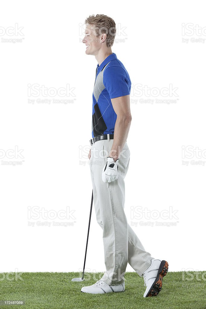Smiling golfer standing with a golf club royalty-free stock photo
