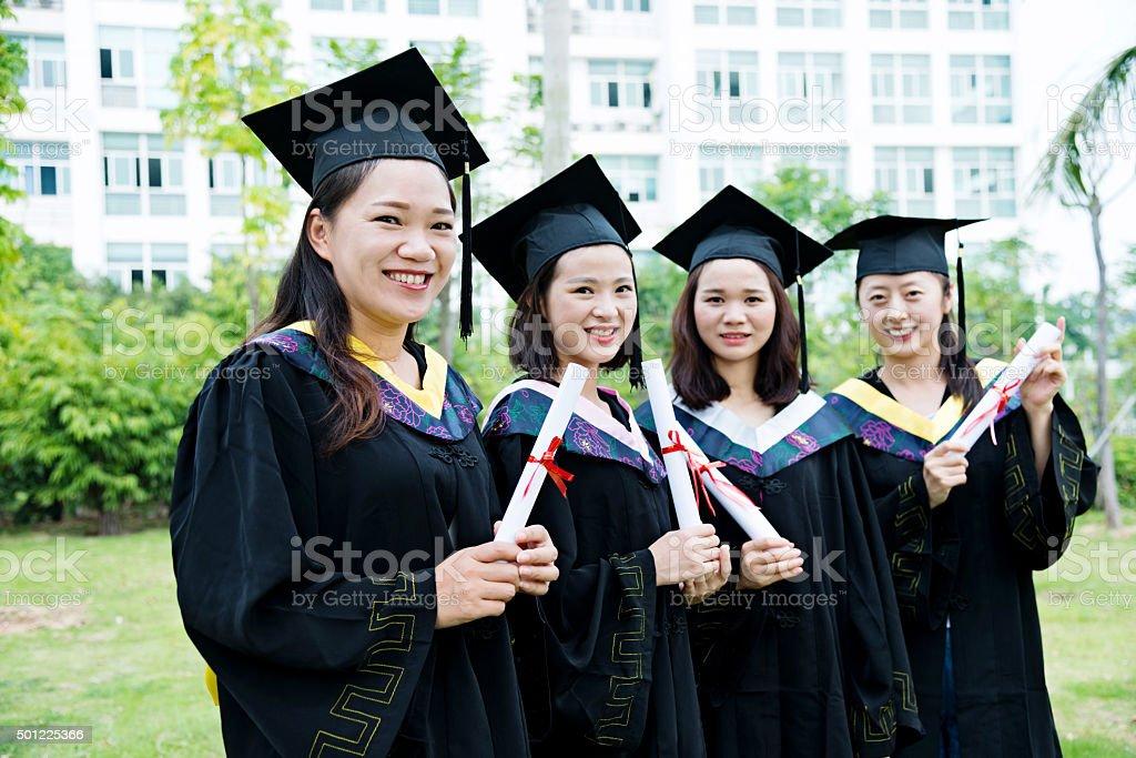Smiling graduates together stock photo