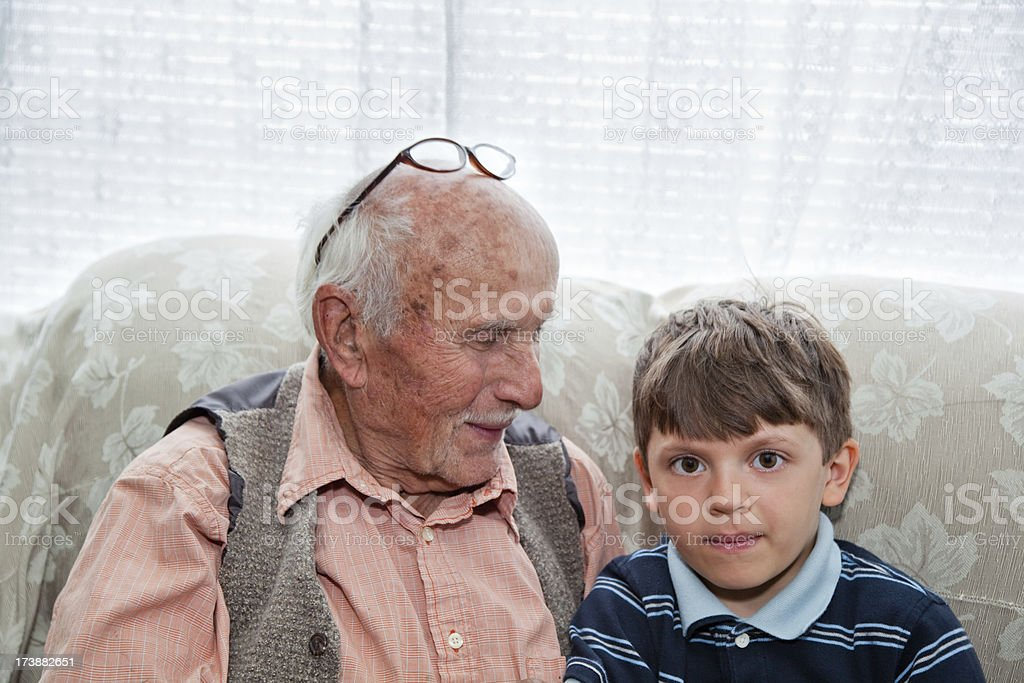 Smiling grandfather looking at grandson on couch. royalty-free stock photo