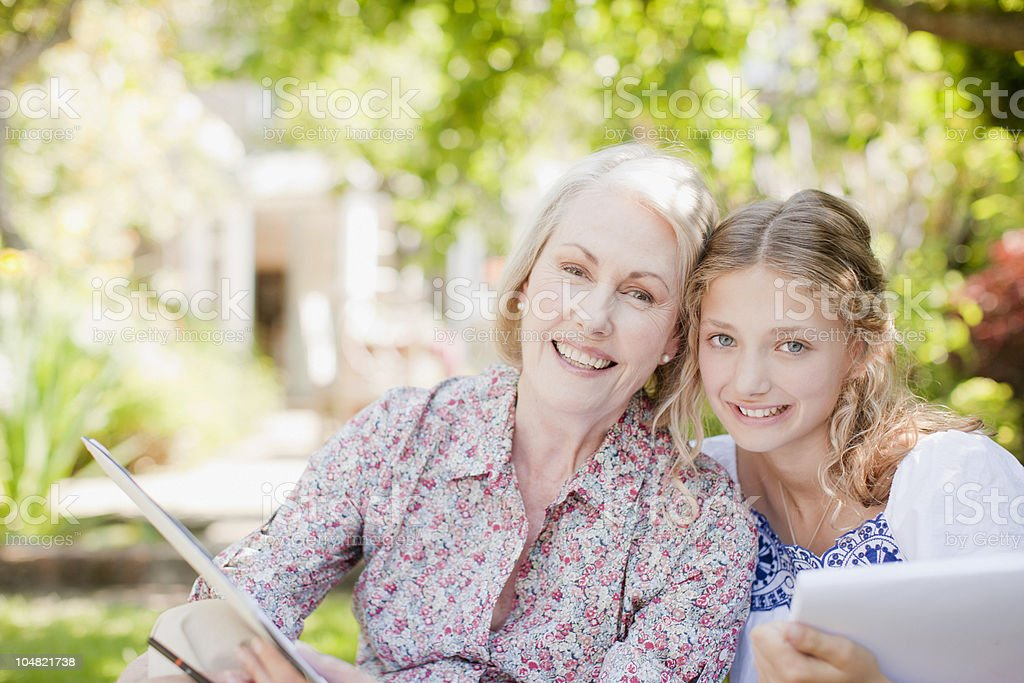 Smiling grandmother and granddaughter holding sketch pads royalty-free stock photo