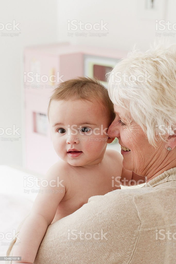 Smiling grandmother holding baby royalty-free stock photo