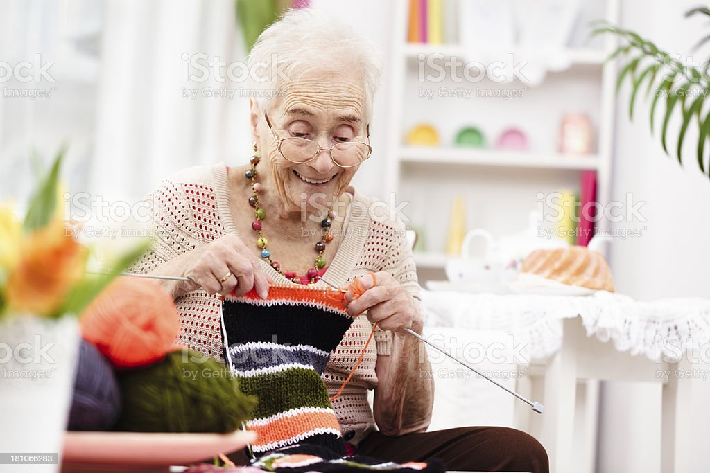 Smiling grandmother knitting royalty-free stock photo