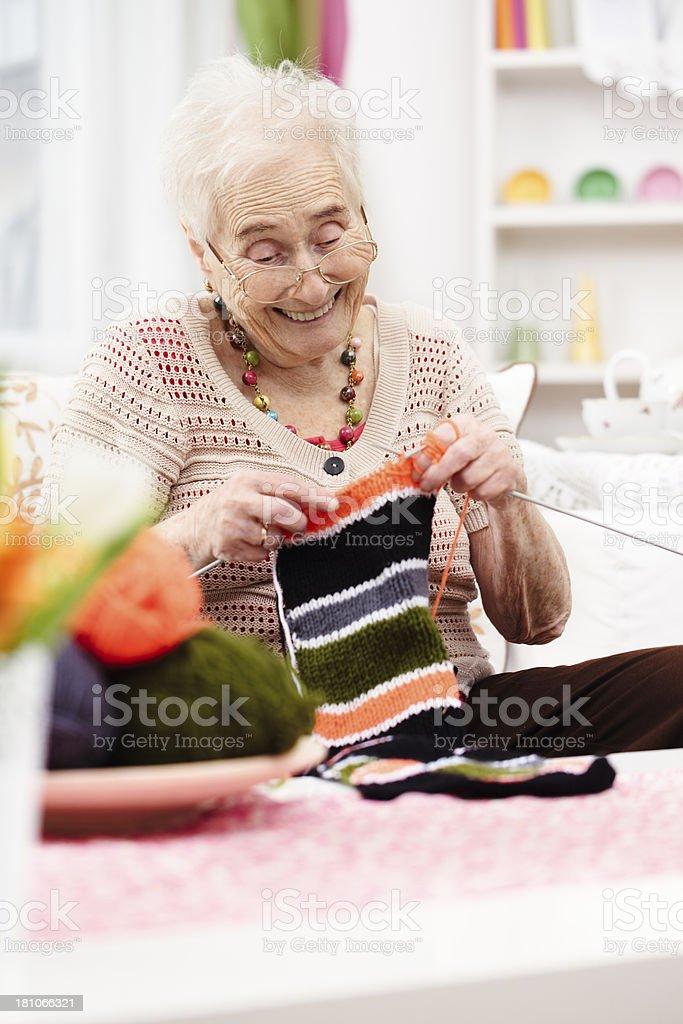 Smiling grandmother knitting royalty-free stock photo