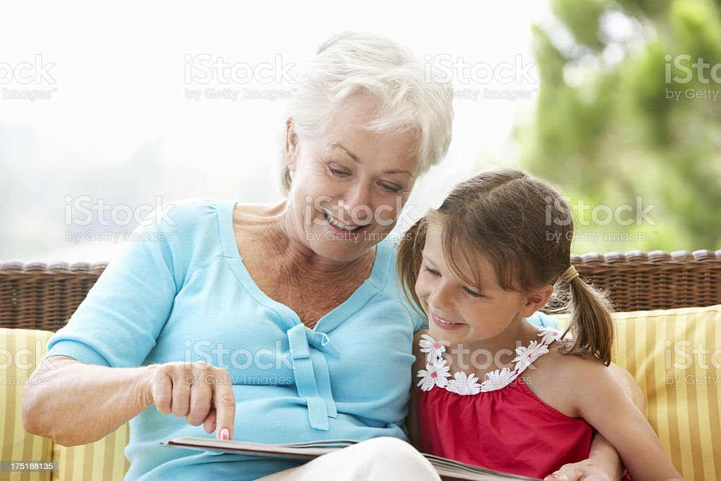 Smiling grandmother reading book with granddaughter stock photo