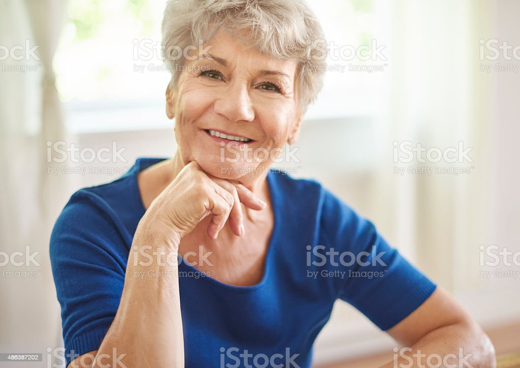 Smiling grandmother sitting at the table stock photo
