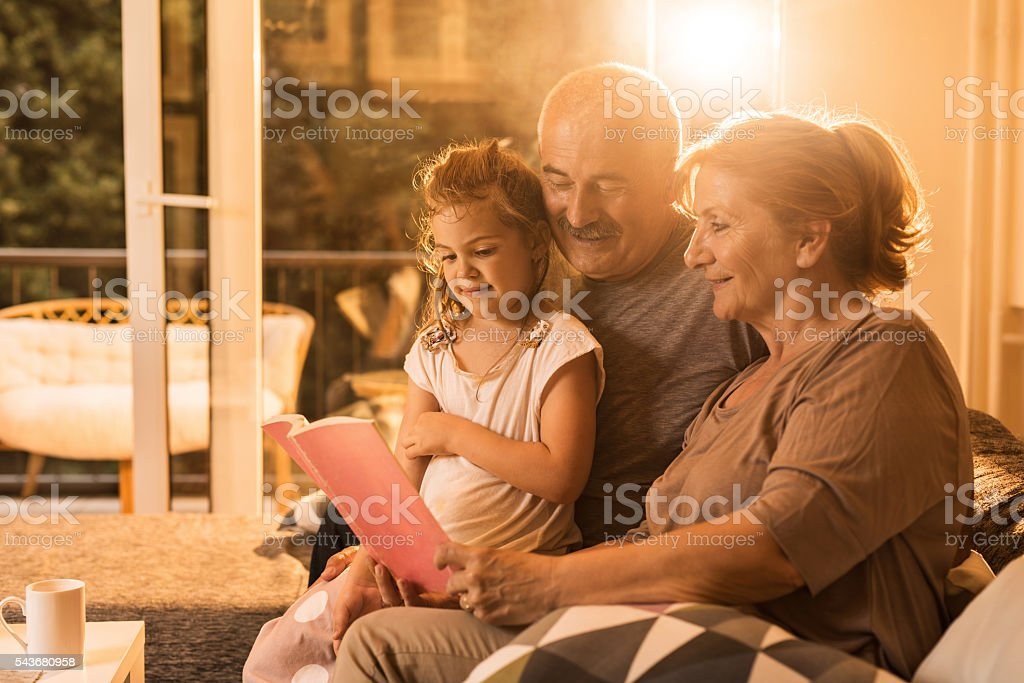 Smiling grandparents reading a book to their granddaughter at home. stock photo