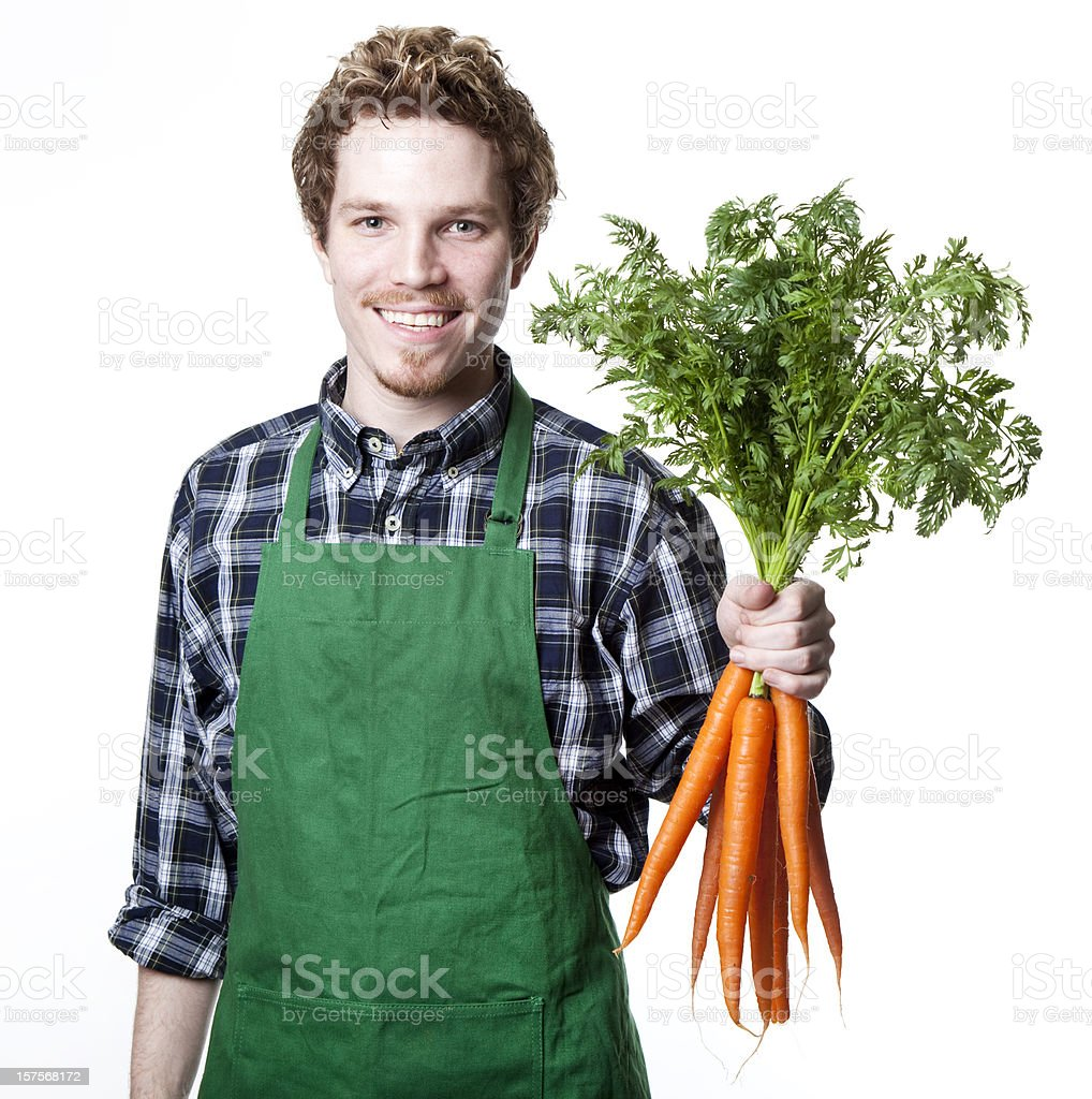 smiling green grocer with bunch of carrots royalty-free stock photo