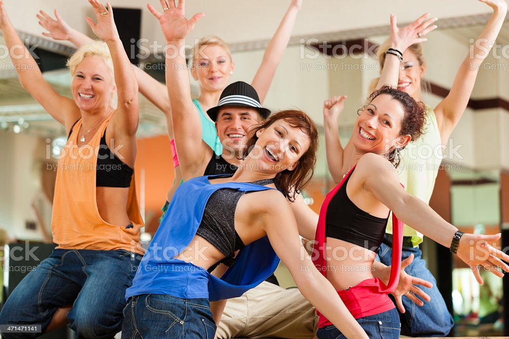 Smiling group of dancers with arms up at a studio stock photo