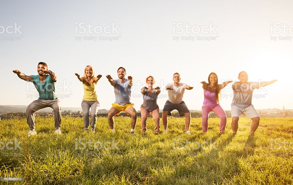 Smiling group of people doing squats and exercising in nature. stock photo