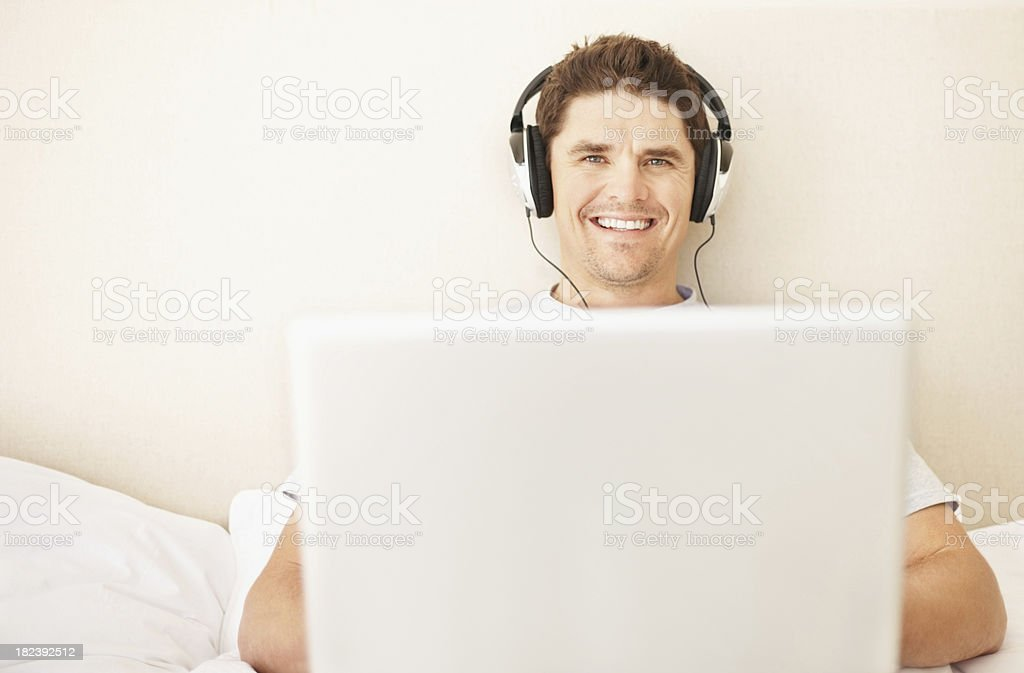 Smiling guy listening to music while using laptop royalty-free stock photo