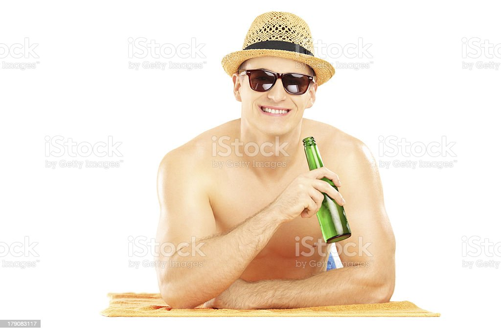 Smiling guy lying on a towel and drinking beer royalty-free stock photo
